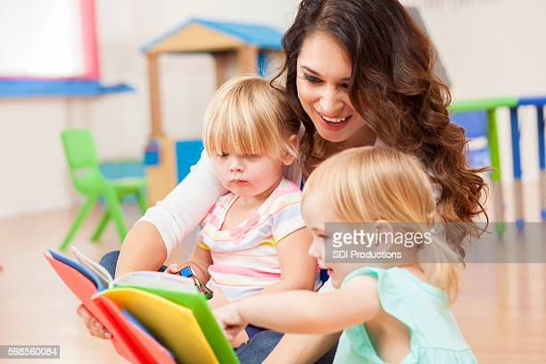 Daycare teacher reading to cute toddler girls