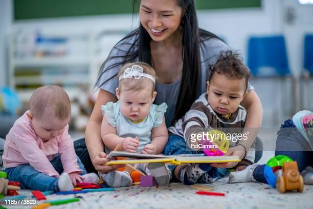 asilo nido seduto sul pavimento lettura ai bambini foto d'archivio - servizi per l'infanzia foto e immagini stock