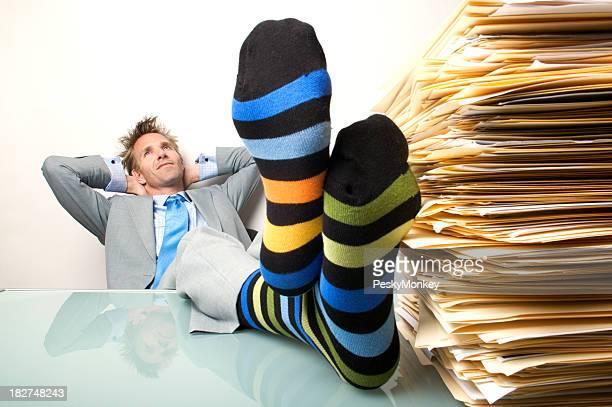 Uomo d'affari Sognare ad occhi aperti ufficio lavoratore mettendo Calze a righe piedi scrivania