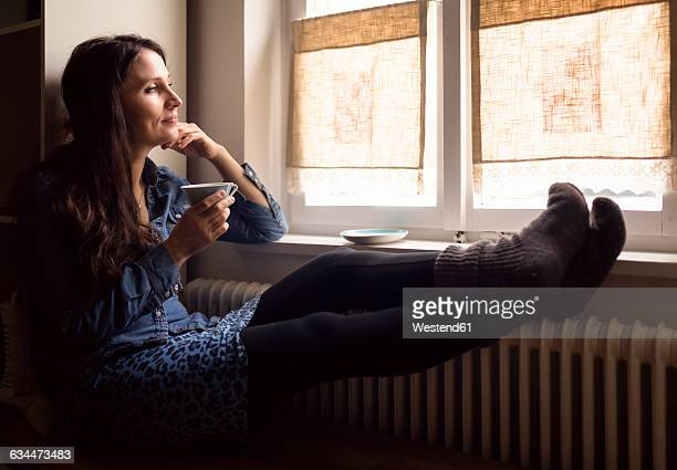 daydreaming woman with feet on the heater drinking cup of tea while looking through window - calor fotografías e imágenes de stock
