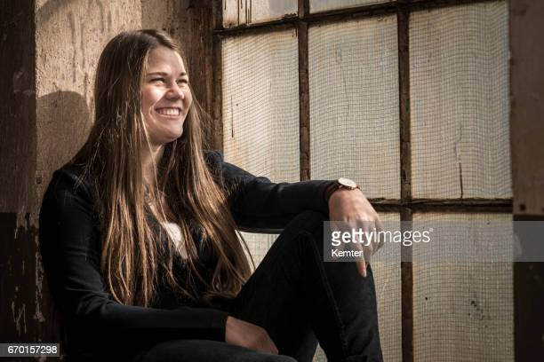 daydreaming young woman sitting at old window looking happy