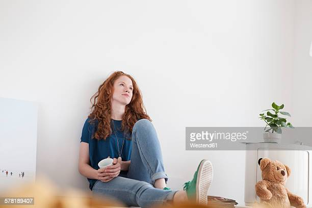 Daydreaming young woman sitting on floor of her living room