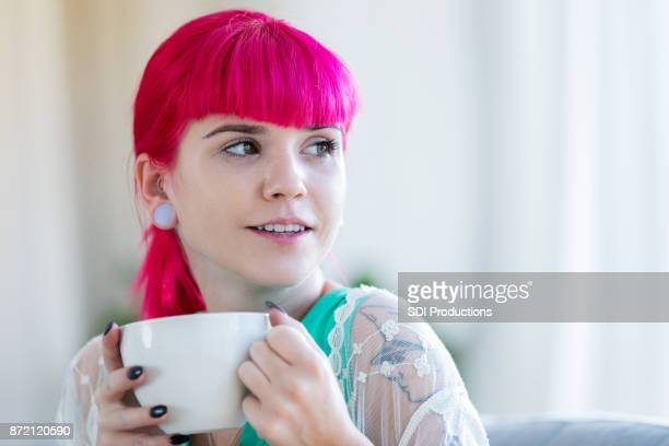 daydreaming young woman with pink hair enjoys warm coffee - earlobe stock photos and pictures