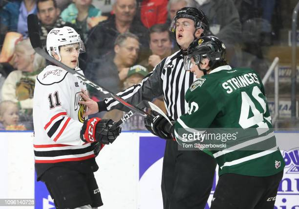 Daylon Groulx of the Owen Sound Attack exchanges slashes with Antonio Stranges of the London Knights in the first period during OHL game action at...