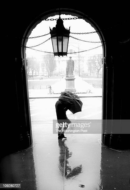Dayna Smith TWP Hunkered down against a driving headwind a pedestrian walks by a picturesque doorway in front of the Smithsonian's Information...