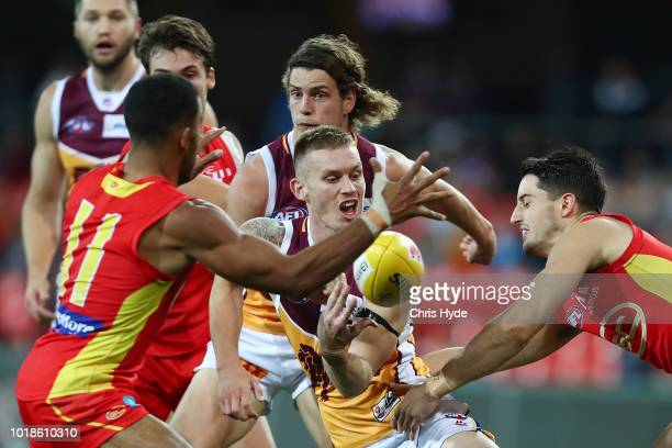 Dayne Beams of the Lions handballs during the round 22 AFL match between the Gold Coast Suns and Brisbane Lions at Metricon Stadium on August 18 2018...