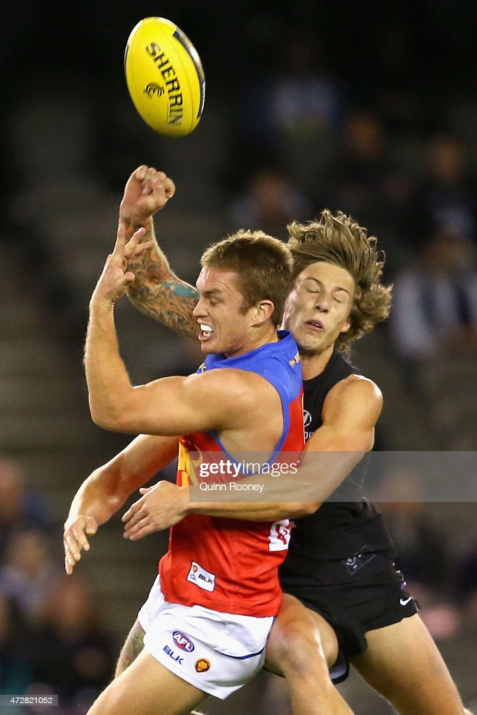 Dayne Beams of the Lions handballs whilst being tackled Mark Whiley of the Blues during the round six AFL match between the Carlton Blues and the Brisbane Lions at Etihad Stadium on May 10, 2015 in Melbourne, Australia.