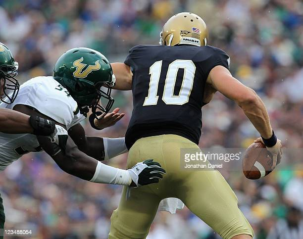 Dayne Crist of the Notre Dame Fighting Irish is sacked by Julius Forte of the University of South Florida Bulls at Notre Dame Stadium on September 3,...