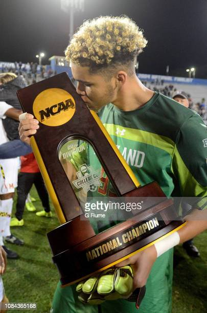 Dayne St Clair of the Maryland Terrapins kisses the trophy after defeating the Akron Zips during the Division I Men's Soccer Championship held at...