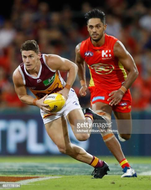 Dayne Zorko of the Lions is chased by Aaron Hall of the Suns during the 2017 AFL round 01 match between the Gold Coast Suns and the Brisbane Lions at...