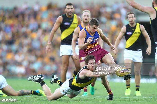 Dayne Zorko of the Lions kicks past Reece Conca of the Tigers during the round four AFL match between the Brisbane Lions and the Richmond Tigers at...