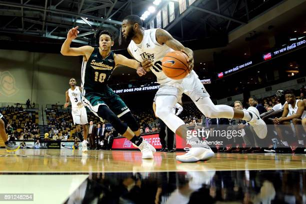 Dayon Griffin of the UCF Knights drives to the net past Eddy Polanco of the Southeastern Louisiana Lions during a NCAA basketball game at the CFE...