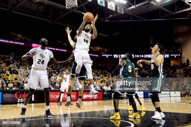 Dayon Griffin of the UCF Knights drives to the net past Jordan Capps and Jabbar Singleton of the Southeastern Louisiana Lions during a NCAA...