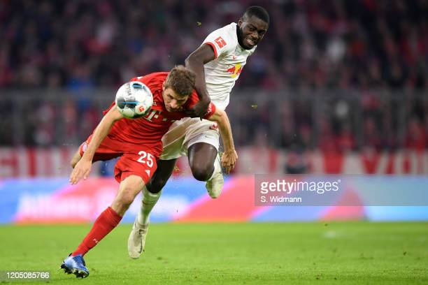 Dayot Upamecano of Leipzig and Thomas Mueller of Bayern Muenchen compete for the ball during the Bundesliga match between FC Bayern Muenchen and RB...