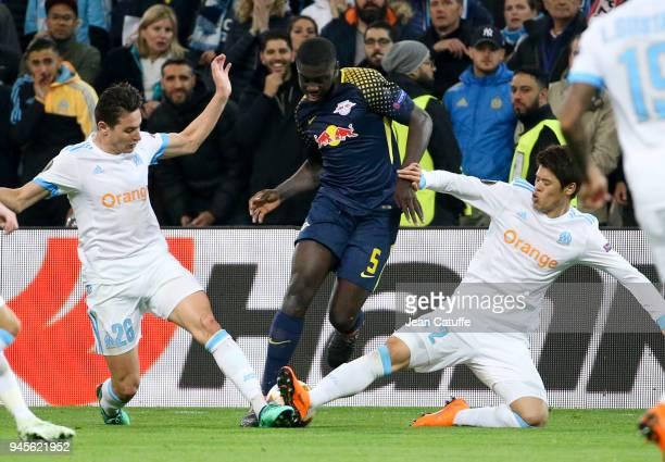 Dayot Upamecano of RB Leipzig between Florian Thauvin and Hiroki Sakai of OM during the UEFA Europa League quarter final leg two match between...