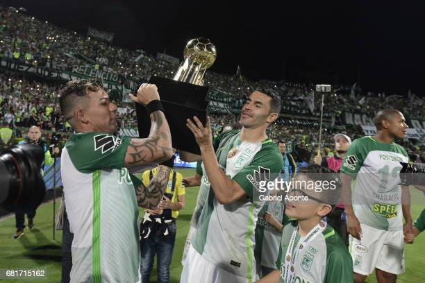 Dayro Moreno and Francisco Najera of Nacional lift the trophy to celebrate after winning a match between Atletico Nacional and Chapecoense as part of...