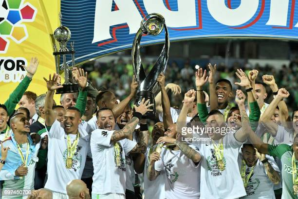 Dayro Moreno of Atletico Nacional lifts the trophy with teammates to celebrate after winning the Final second leg match between Atletico Nacional and...