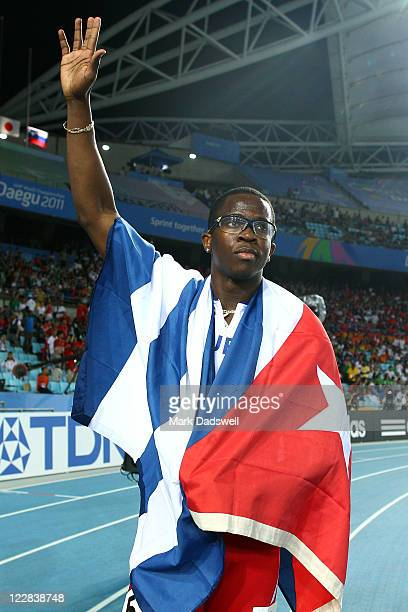 Dayron Robles of Cuba celebrates with his country's flag after winning the men's 110 metres hurdles final during day three of the 13th IAAF World...