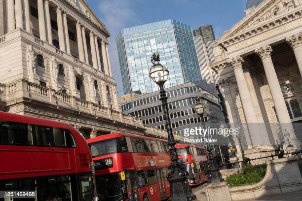 Days before the Chancellor Rishi Sunak delivers his Budget, buses queue at red lights with a wide view of the Bank of England and Royal Exchange in...