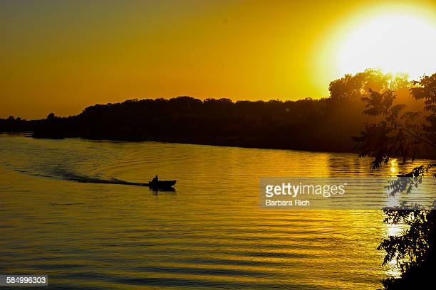 Day's end on the river with boat silhouette