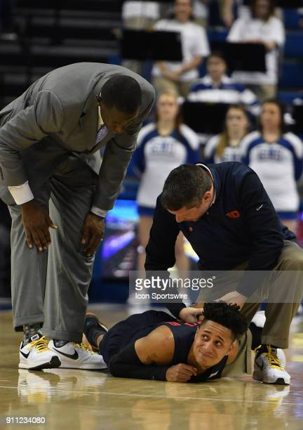Dayton Flyers basketball coach Anthony Grant looks on as a Dayton trainer looks after Dayton Flyers guard Darrell Davis during a Atlantic Ten...