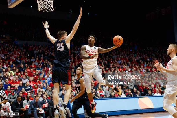 Dayton Flyers guard John Crosby lays the ball up while Pennsylvania Quakers forward AJ Brodeur defends during the second half of a game between the...