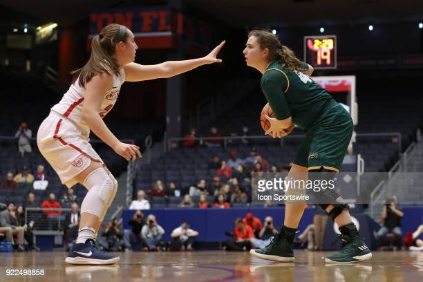 Dayton Flyers guard Lauren Cannatelli puts up a hand in the face of George Mason Patriots guard Sarah Kaminski in a game between the Dayton Flyers...