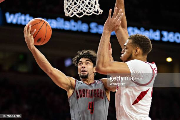 Dayton Gumm of the Austin Peay Governors drives to the basket against Daniel Gafford of the Arkansas Razorbacks at Bud Walton Arena on December 28...