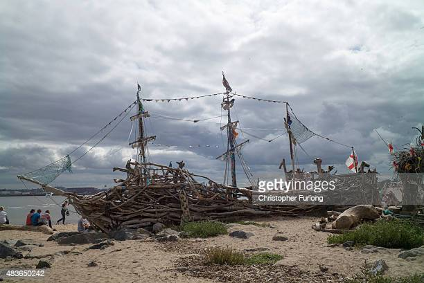 Daytrippers and children on the Summer break from school enjoy the Black Pearl pirate ship art installation which is made from driftwood at New...