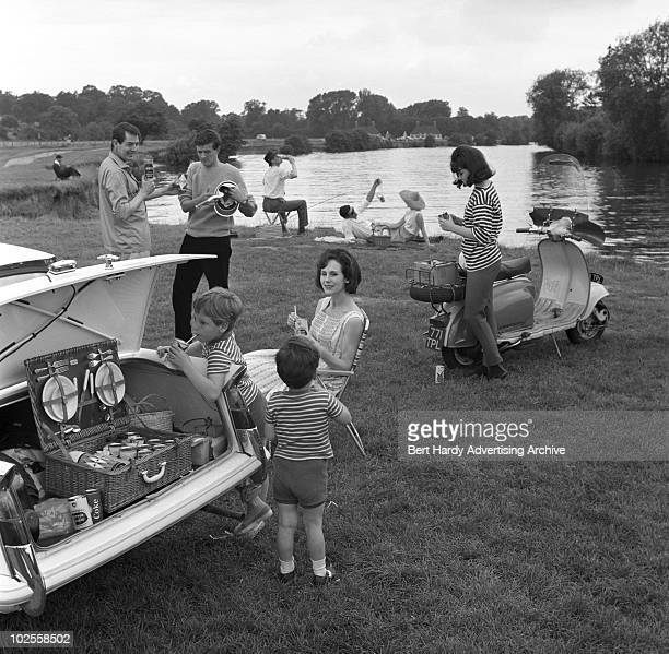Daytrippers enjoying a picnic by a river, 11th July 1963.