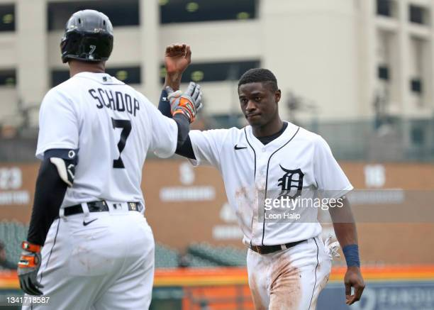 Daz Cameron of the Detroit Tigers scores and celebrates with his teammate Jonathan Schoop during the third inning of the game against the Chicago...