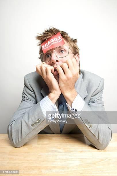 Dazed Businessman Sits at Desk w Fragile Sticker