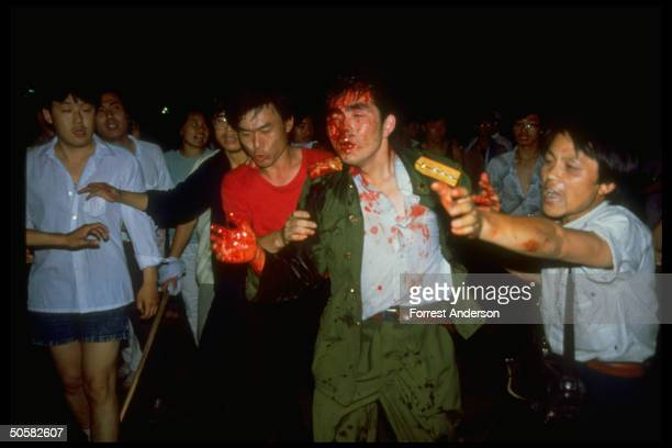 Dazed soldier covered in blood from head wound being helped and escorted by prodemocracy student protestors Tiananmen Sq