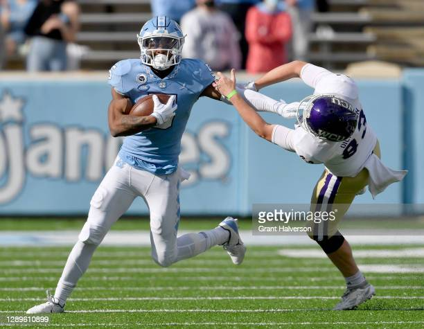 Dazz Newsome of the North Carolina Tar Heels stiff-arms Brandon Dickerson of the Western Carolina Catamounts during their game at Kenan Stadium on...