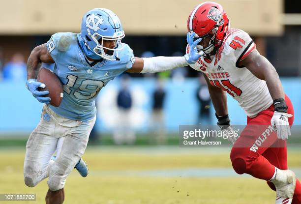 Dazz Newsome of the North Carolina Tar Heels stiffarms Isaiah Moore of the North Carolina State Wolfpack during the second half of their game at...