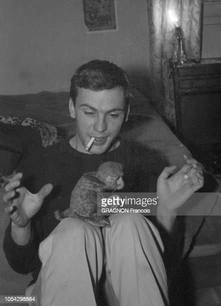 Décembre 1958 Rendezvous avec JeanLouis TRINTIGNANT attitude souriante du comédien une cigarette aux lèvres jouant avec jouet mécanique un petit...