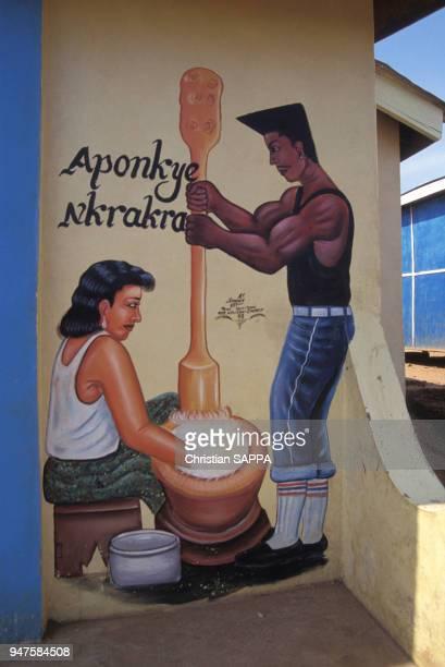 Décoration à l'extérieur d'un café un homme et une femme autour d'un pilon au Ghana