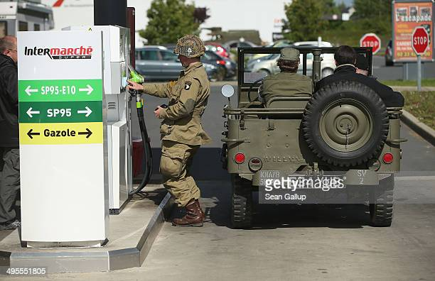 Day historical reenactment enthusiasts dressed as US soldiers stop to buy gas for their World War IIera jeep on June 4 2014 at Carentan France Friday...