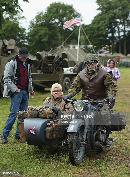 Day reenactment enthusiasts dressed as Allied soldiers ride a World War IIera motorcycle and sidecar through a reenactment camp on June 4 2014 in...