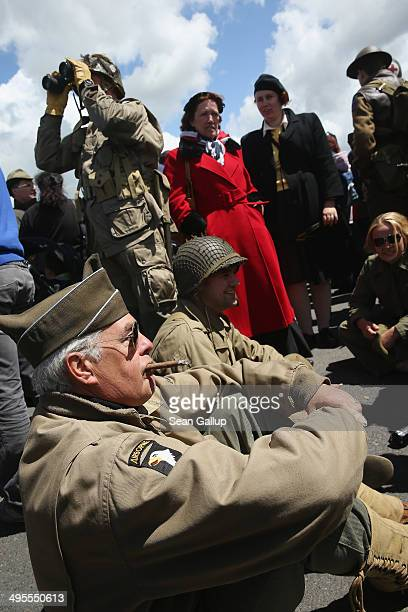 Day reenactment enthusiasts dressed as World War II American soldiers attend a planned parachute drop on June 4 2014 at Carentan France Friday the...