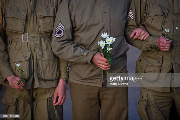 Day reenactment enthusiasts dressed as World War II American soldiers hold flowers during a gathering on the Omaha Beach to commemorate the...