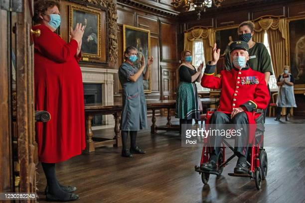 Day veteran and Chelsea Pensioner Bob James Sullivan a resident at the Royal Hospital Chelsea, is applauded by staff after receiving an injection of...