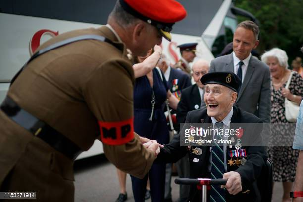 Day veteran Lewis Banham aged 96 is greeted by a military policeman as he arrives at a function at Southwick House which in June 1944 was the...