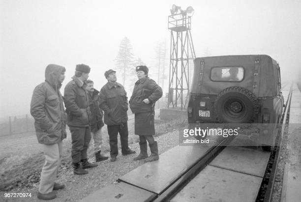 DDRGrenzsoldaten inspizieren mit DDRBürgerrechtlern die Grenzsicheurngsanlagen rund um den Brocken aufgenommen im Januar 1990 Der Brocken im Harz war...