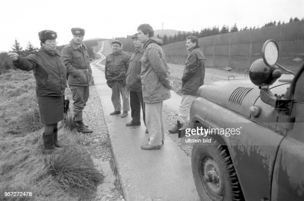 DDRGrenzsoldaten inspizieren mit DDRBürgerrechtlern die Grenzsicheungsanlagen rund um den Brocken aufgenommen im Januar 1990 Der Brocken im Harz war...