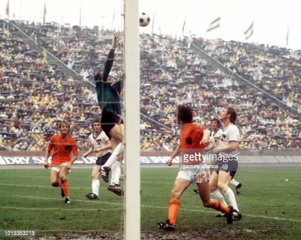 Torhüter Jürgen Croy streckt sich im strömenden Regen nach einem Flankenball. Die niederländischen Stürmer Johan Neeskens und Rob Rensenbrink laufen...