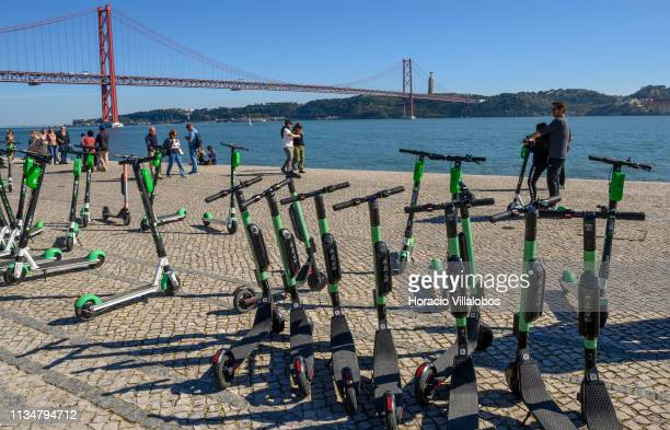 25 de Abril bridge can be seen in the distance while a man and a child ride an escooter in front of a number of escooters parked near MAAT museum by...