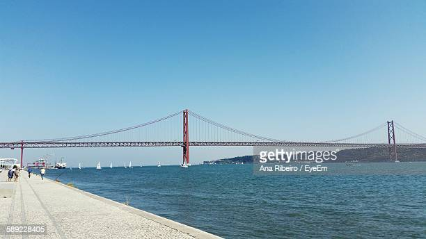 25 De Abril Bridge Over Tagus River Against Clear Blue Sky