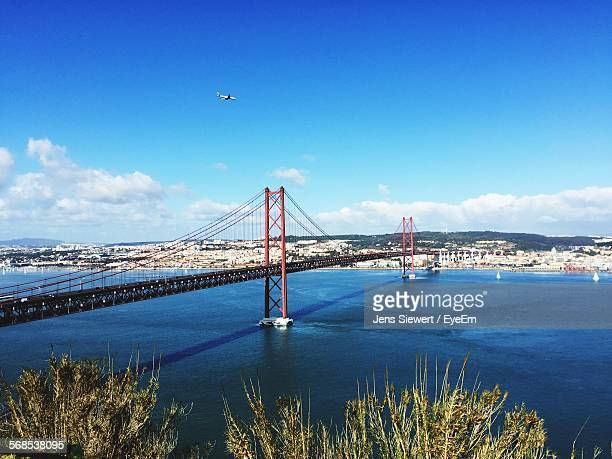 25 De Abril Bridge Over Tagus River Against Sky In City