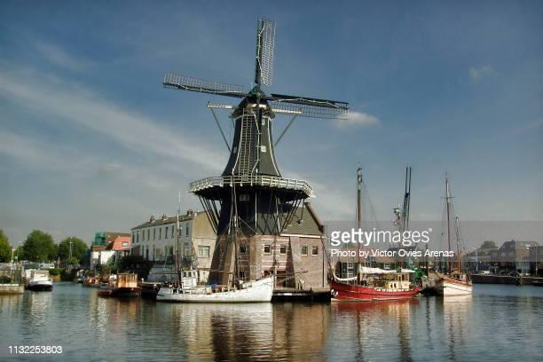 de adriaan windmill (molen) and boats on the banks of the river spaarne is a landmark of the historic city of haarlem, netherlands - haarlem fotografías e imágenes de stock